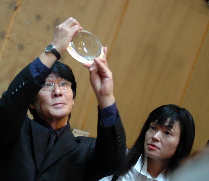 Daido Moriyama holds the award: a gold mounted lens